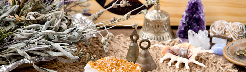 An altar for the Solar Eclipse filled with crystals, sage and tarot is on a table.
