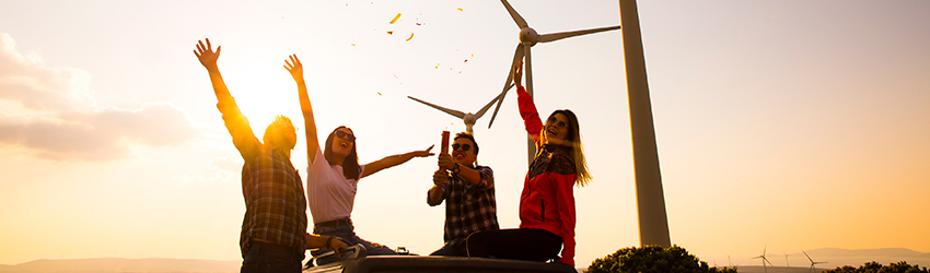 Four friends sit in the sun in front of wind turbines.