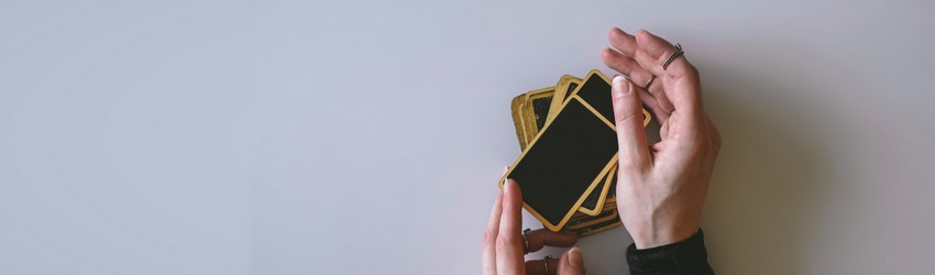 A woman gets ready for a tarot reading with black tarot cards that have a gold rim.