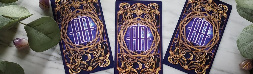 Three tarot cafrds face down on a marble white table. They are purple and have the letters AA on them (standing for Astrology Answers.)
