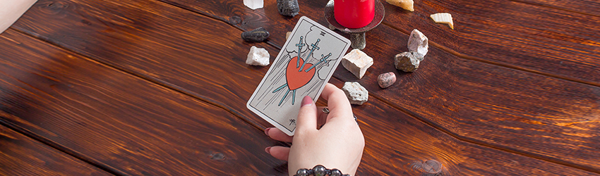 A person holding a Tarot card in front of a red candle.