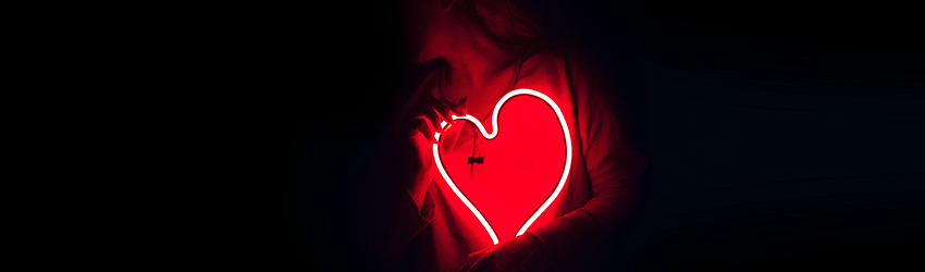 Person holding a heart neon sign.