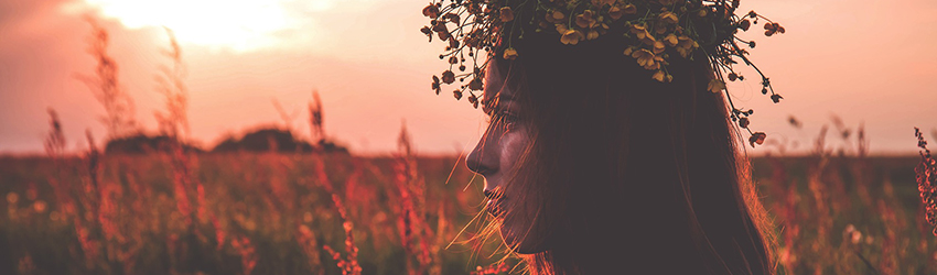 A woman stands in a canola field. She is wearing a flower crown and facing to the left of the frame.