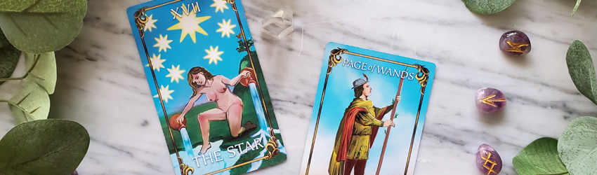 Tarot cards for Aquarius displayed on the Astrology Answers Master Tarot Deck. The Star and the Page of Wands are displayed on a white marble surface with green leaves around it and purple amethyst runes.