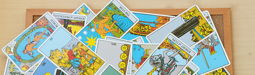 A bunch of Tarot cards on a tray messily splayed out.