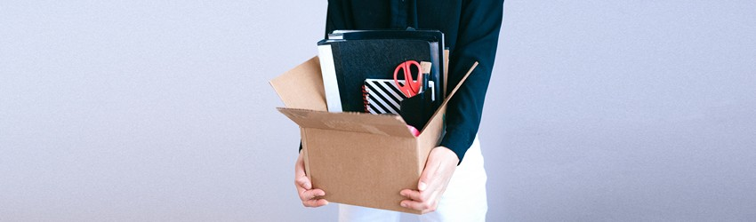 A person is holding their stuff that was on their desk in a box because they are now unemployed.
