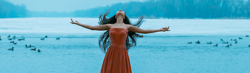 A woman is in front of the ocean. She throws her head back to release negative energy.