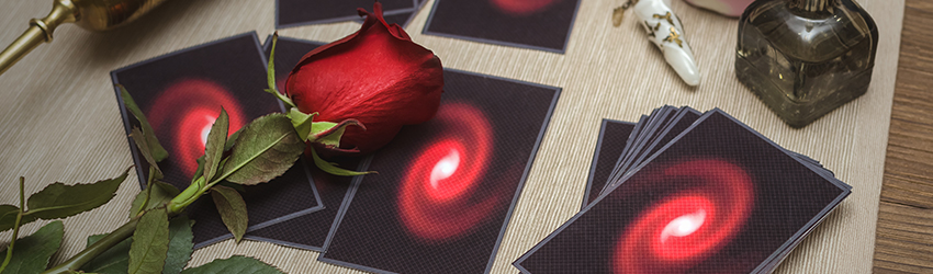 Tarot cards lay on a table with a romantic red rose on top of the spread.