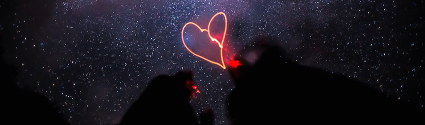 Two people stand in front of a pink heart neon light and purple smoke holding hands.