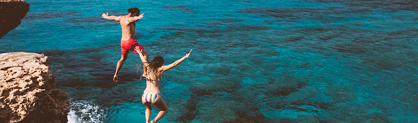 Two people jump into the ocean with their arms in the air.