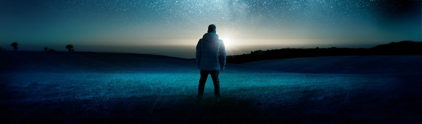 A man in winter gear stands under a navy blue night sky.