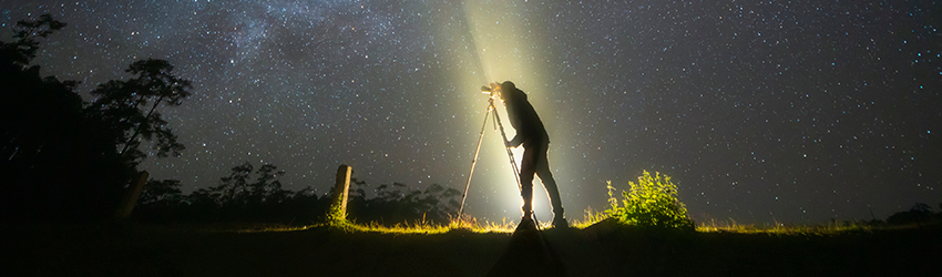A man stands in front of a starry sky.