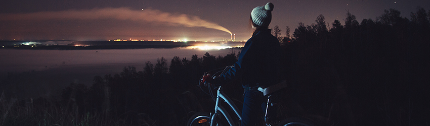 A woman on a bike looks at the stars.