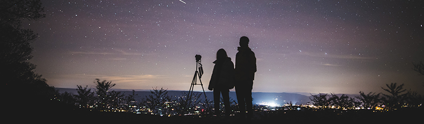 Two people stand on a mountain top next to a telescope looking at the stars. The sky is purple.
