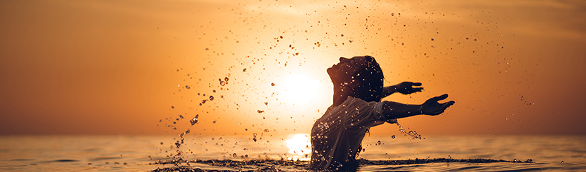 A person swimming in the ocean during an orange sunset. They are throwing their hair back and opening their arms to the sky.