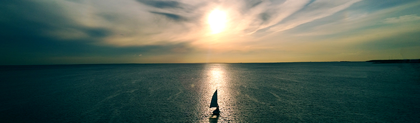 A person is sailing at dusk.