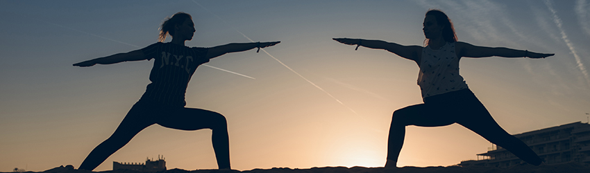 Two women do yoga on a hill in front of a sunset.