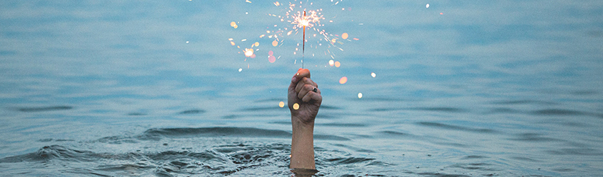 Person holds sparkler while fully submerged in water to the forearm.