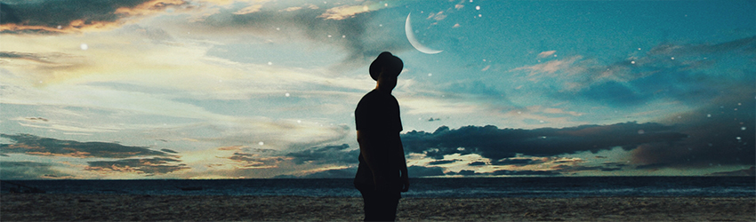 A person stands under a new moon on a beach.