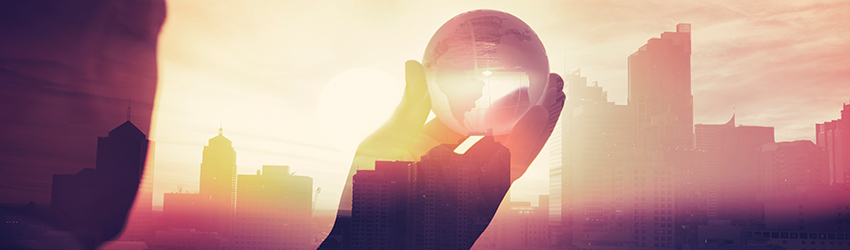 A man holds a globe in front of a city landscape.