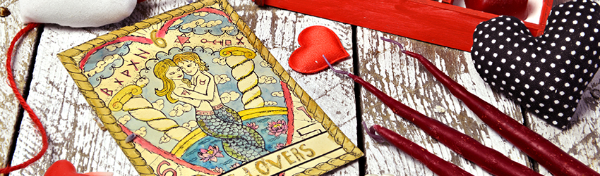 A love tarot spread on a table surrounded in heart shaped chocolates.