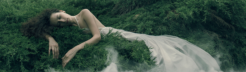 A woman is growing out of the earth. She is covered in moss.