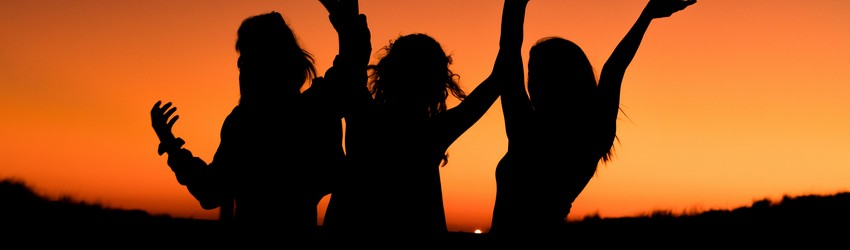 Three women are dancing together as the sun sets on an orange sky.