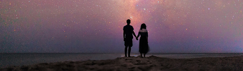 A couple holds hands in front of a purple starry sky.