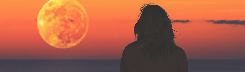 A woman looks in the distance at a large red sun.