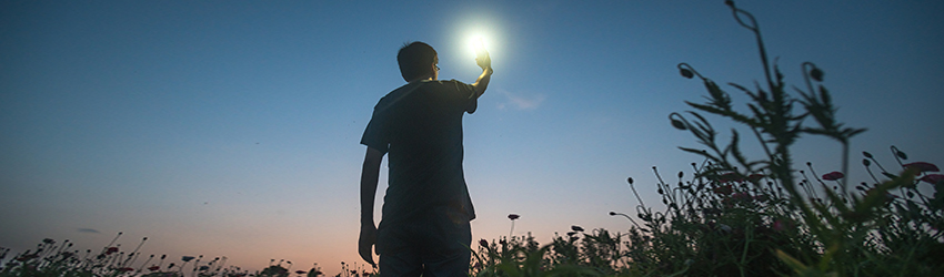 A man holds a light to the blue sky in order to find the way.