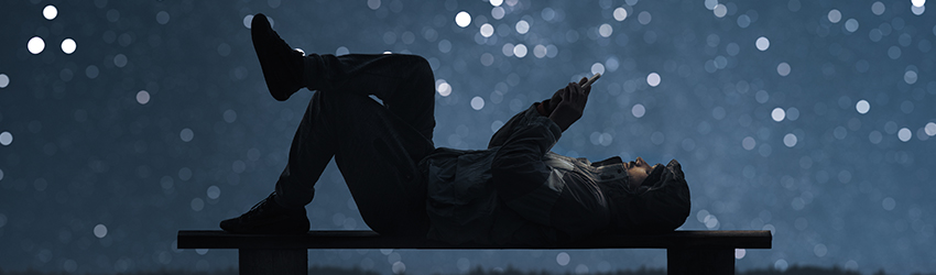 A person lays on their back texting in front of a sky full of stars.