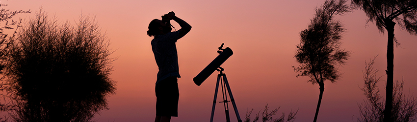 A person looks up to the sky with binoculars.