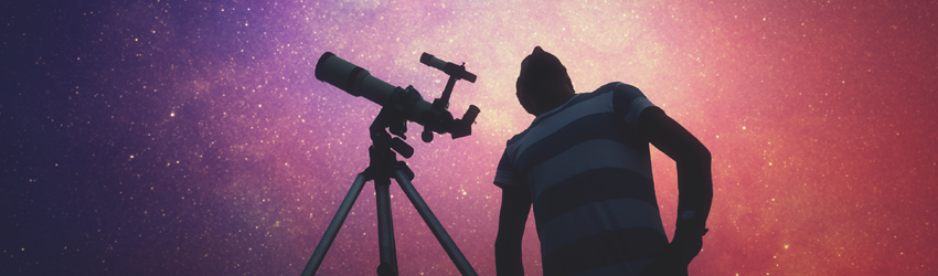 Person looking through a telescope at the stars above.