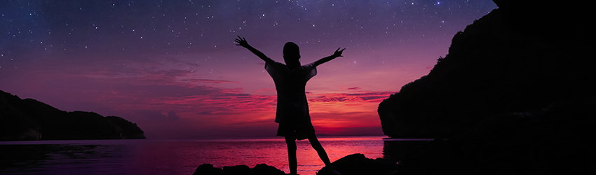 A silhouette of a woman is standing with her arms open in front of the ocean. The sky is filled with a beautiful pink and blue sunset.