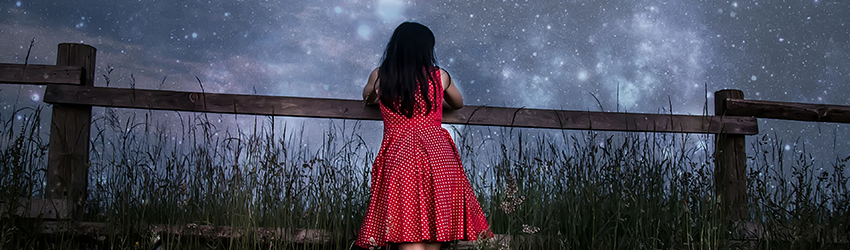 A person leaning on a fence looking at the stars.