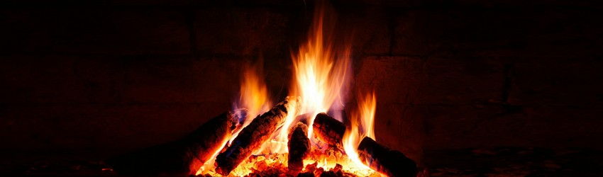 A fireplace with a traditional yule log in it.
